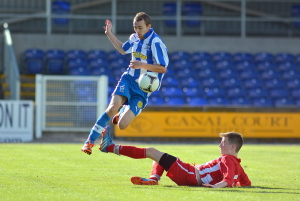 Newry striker Mark Lowry escapes this challenge from Loughgall's Ross Wilson